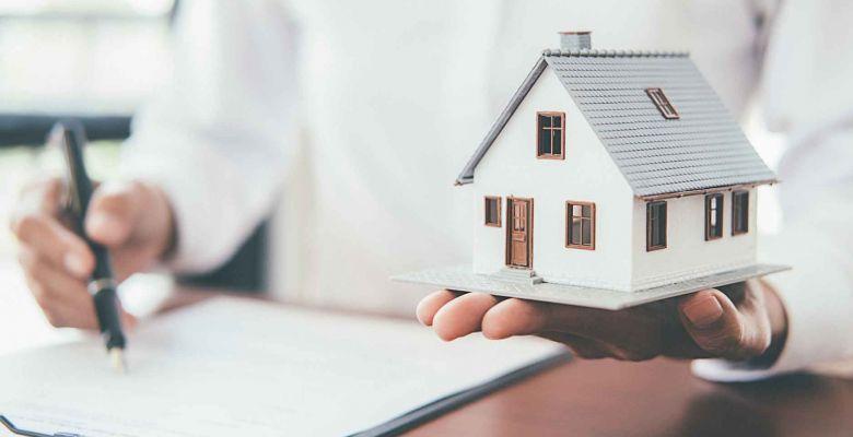 Una persona sostiene una vivienda en su mano